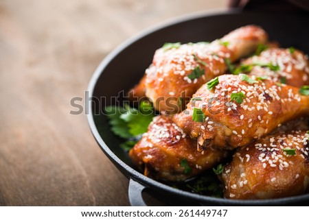 Baked spicy chicken legs with sesame and parsley in cast iron frying pan on dark wooden background close up. - stock photo
