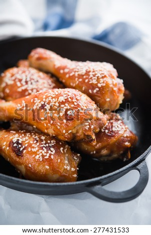 Baked spicy chicken legs with sesame in cast iron frying pan on white background close up. Asian food. - stock photo