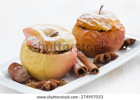 baked stuffed apples on a plate on white wooden table, close-up, horizontal - stock photo