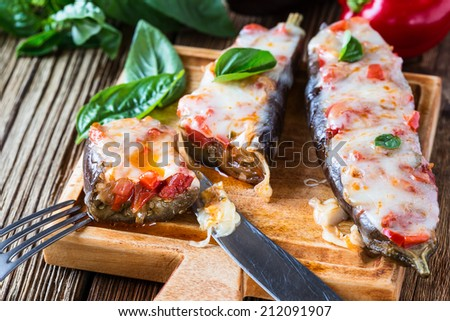 Baked stuffed eggplant with cheese and tomatoes on rustic wooden table, vegetarian food - stock photo