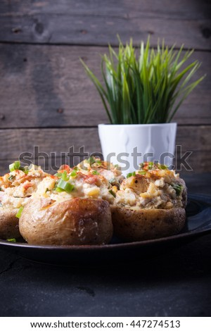 Baked stuffed potatoes with bacon, eggs and chives on a plate - stock photo