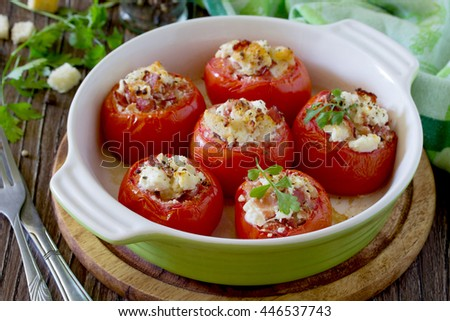Baked stuffed tomatoes with bacon and feta cheese on a wooden table - stock photo