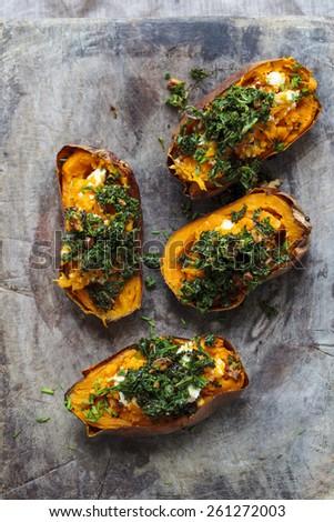 Baked sweet potato with crispy kale, walnuts and feta cheese - stock photo