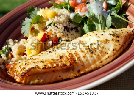 Baked tilapia served with arugula and quinoa salad - stock photo
