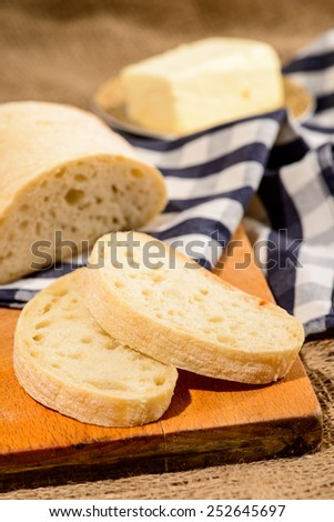 Baked to perfection. Top view of a sliced home-baked bread ciabatta on a wooden board and a piece of butter on the background with a farm style checkered napkin and sackcloth - stock photo