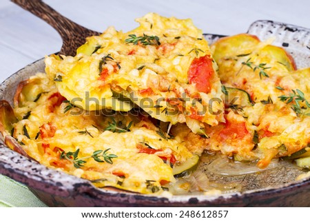 Baked Tomatoes, Zucchini and Potatoes with Thyme and Parmesan  - stock photo