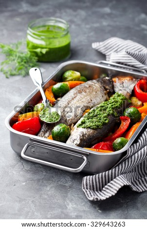 Baked trout with vegetables and dill pesto, selective focus - stock photo