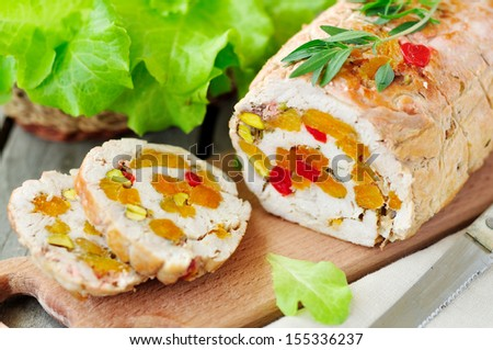 Baked turkey roll stuffed with dried apricots, cherries and pistachios, shallow depth of field, selective focus - stock photo