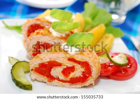 baked turkey roulade stuffed with cheese and red pepper for dinner  - stock photo