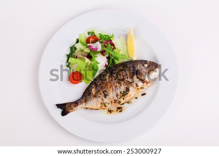 baked whole fish grilled on a plate with vegetables and lemon on top for the menu - stock photo