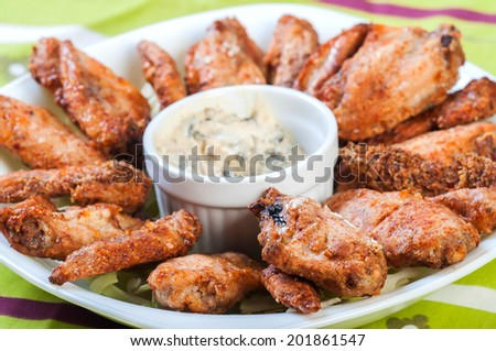 baked wings with sour cream sauce - stock photo