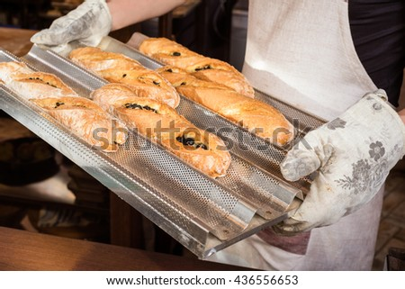 baker concept. closeup of some baguettes or bread rolls on a tray in bakery. Fresh baguettes with olive - stock photo