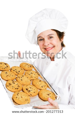 Baker holding up a tray of fresh hot chocolate chip cookies.  Isolated on white.   - stock photo