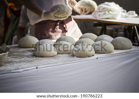 Baker making artisan bread in a medieval fair - stock photo