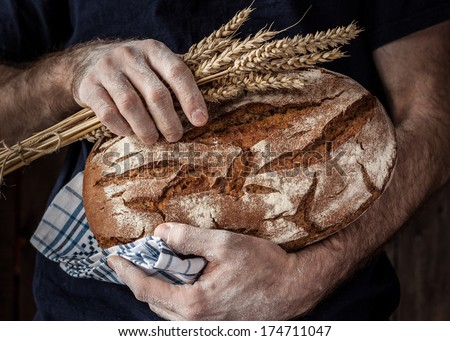 Baker man holding rustic organic loaf of  bread and wheat in hands - rural bakery. Natural light, moody still life. - stock photo