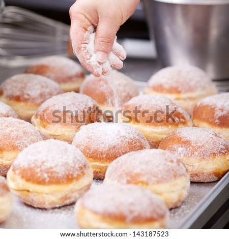 Baker pours sugar over pastry on a bakery tray - stock photo