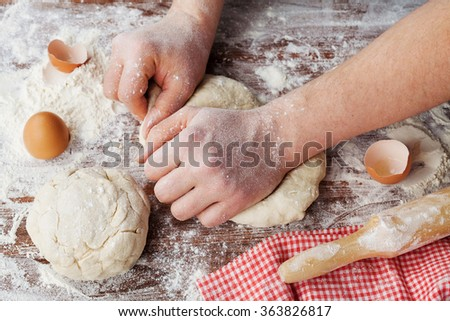 Baker prepares the dough on a wooden table, chef knead the dough with flour, homemade dough for bread or pizza, top view, rustic style - stock photo