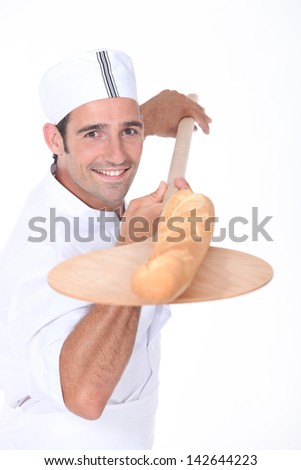 Baker pulling a freshly baked baguette out from the oven - stock photo