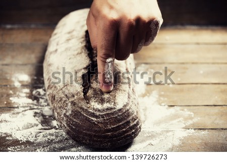 Baker's hands pointing on a bread. Photo with high contrast - stock photo