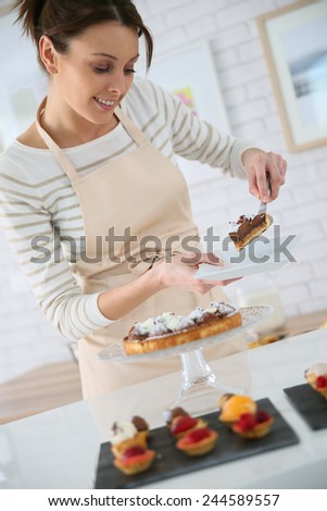 Baker serving piece of tart to customer - stock photo