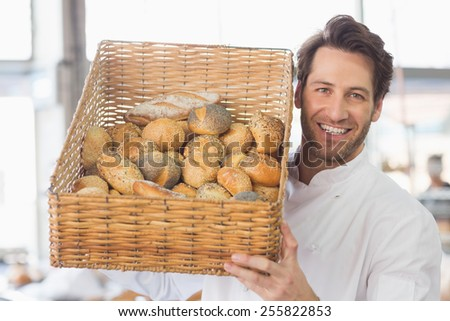 Baker showing basket of bread in the kitchen of the bakery - stock photo