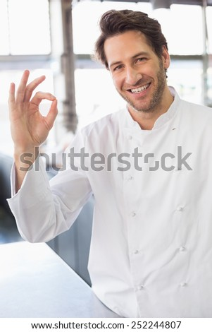 Baker smiling at the camera in the kitchen of the bakery - stock photo