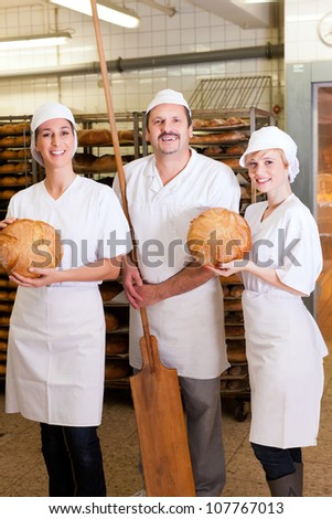 Baker standing with his team in bakery with freshly baked bread - stock photo