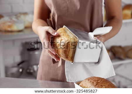 Baker with freshly baked bread in kitchen of bakery - stock photo