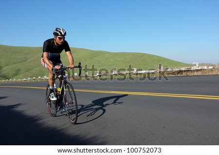 BAKERSFIELD, CA - APR 21: An unidentified rider strains uphill during the mountainous Vlees Huis Professional  Road Race on April 21, 2012, in Bakersfield, California. - stock photo