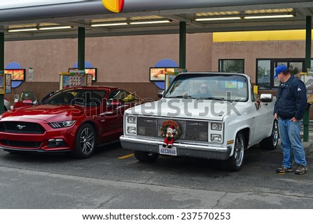 BAKERSFIELD, CA - DECEMBER 13, 2014: Classic cars are lined up at a local drive-in to compete for trophies at the Christmas Joy Ride and Toy Run Car Show.  - stock photo