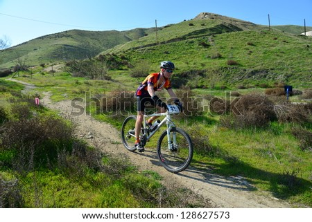 BAKERSFIELD, CA-FEB 17: An unidentified male rider bounces down a steep hill during the Foothill Classic Mountain Bike Race on February 17, 2013, in Bakersfield, California. - stock photo