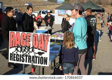 BAKERSFIELD, CA - JAN 11, 2014: An unidentified woman signs up for the race at the 24th Annual Fog Run, misnamed this year since the sun is shining brightly. - stock photo