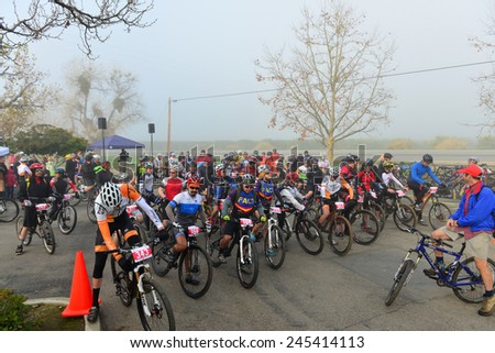 BAKERSFIELD, CA - JAN 17, 2015: Contestants line up at the start of the Rio Bravo Rumble cycling portion of the biathlon (running and mountain biking) under extremely foggy conditions. - stock photo