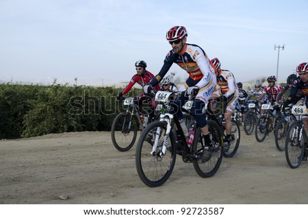 BAKERSFIELD, CA - JAN 14: Cyclists race for position at the start of the Rio Bravo Rumble biathlon (running and mountain biking) on January 14, 2012, in Bakersfield, California. - stock photo