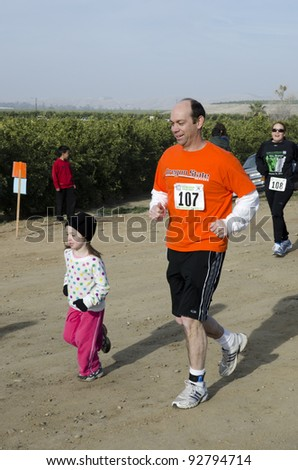 BAKERSFIELD, CA - JAN 14: Father and daughter run the dirt path cross country leg of the Rio Bravo Rumble biathlon (running and mountain biking) on January 14, 2012, in Bakersfield, California. - stock photo