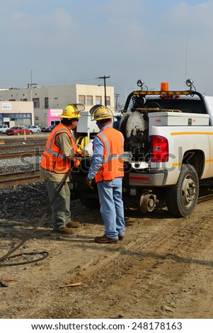 BAKERSFIELD, CA - JANUARY 29, 2015: Two Union Pacific Railroad employees wind air hose onto reel after using pneumatic drill for a job replacing wood ties under rails. - stock photo