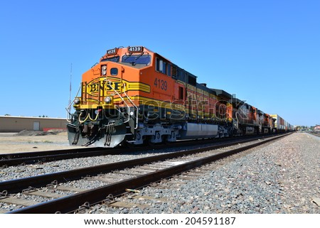 BAKERSFIELD, CA-JULY 11, 2014: A Burlington Northern and Santa Fe diesel-electric locomotive pulls a long train out of the city heading east into the Sierra Nevada Range. - stock photo