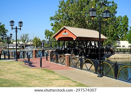 BAKERSFIELD, CA - JULY 17, 2015: An irrigation canal is also used as part of an urban renewal project. Despite the current severe drought, cooling water still flows under the Mill Creek Park bridge. - stock photo