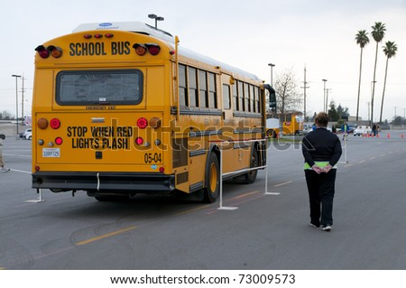 """BAKERSFIELD, CA - MAR 12: The 28th Annual School Bus """"Roadeo"""" tests driver skills on March 12, 2011, in Bakersfield, California. Bus negotiates tricky obstacle course. - stock photo"""