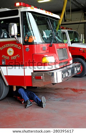 BAKERSFIELD, CA - MAY 21, 2015: A fireman does maintenance work under Truck #215 at the Central Fire Station. - stock photo