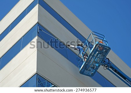 BAKERSFIELD, CA - MAY 2, 2015: Carlos Ruiz works high off the ground on the platform of a man lift to wash the windows of a Kern County office building. - stock photo