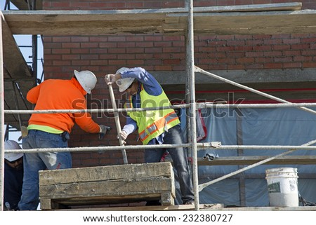 BAKERSFIELD, CA - NOVEMBER 22, 2014: Workmen are elevated on scaffolding, mixing mortar and grouting between courses of exterior brick for a shopping center project. - stock photo