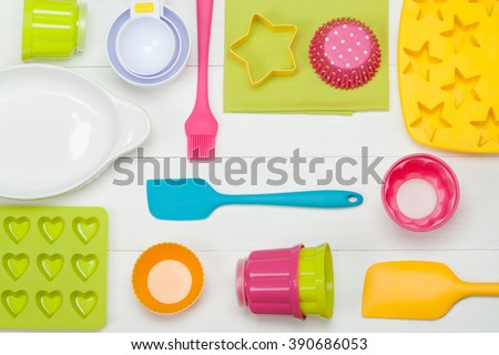 Bakery And Cooking Tools. Silicone Moulds, Cupcake Cases. Measuring Cups. Top View. White Wooden Table. - stock photo