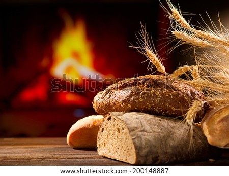 Bakery Bread on a Wooden Table. Various Bread and Sheaf of Wheat Ears Still-life - stock photo