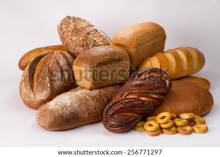 Bakery product assortment with bread loaves, buns, rolls and bagels - stock photo