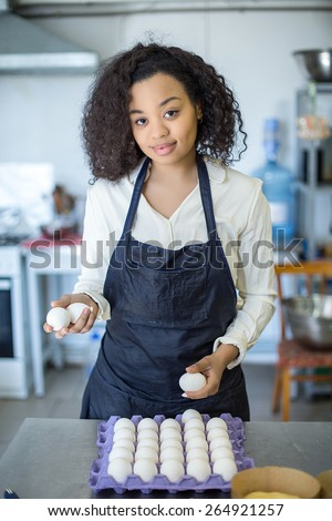 bakery production. bakery, eggs, cook prepares Female baker mixing dough in kitchen - stock photo