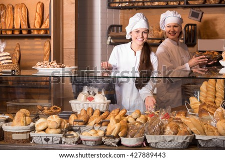 Bakery staff offering bread and different cookies for sale - stock photo
