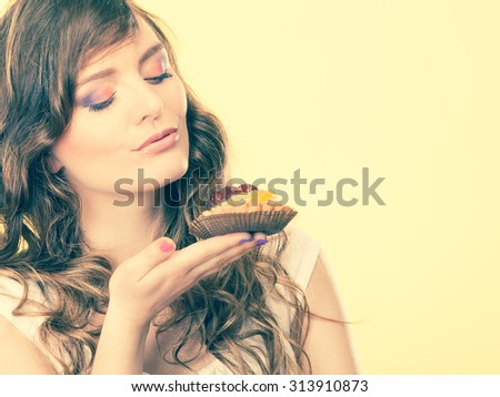 Bakery sweet food indulging and people concept. Cute attractive woman closed eyes holds cake cupcake in hand smelling yellow background - stock photo