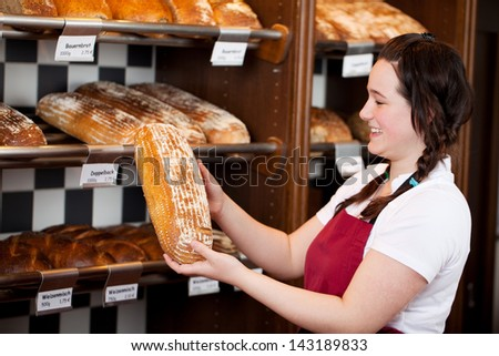 Bakery worker with a loaf of fresh crusty bread in her hands which she is displaying after removing it from the shelf - stock photo