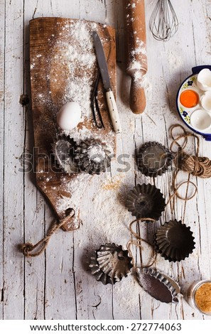 Baking and pastries retro image. Various vintage kitchen utensils, props and ingredients  on a rustic wooden table with flour. Top view.  - stock photo